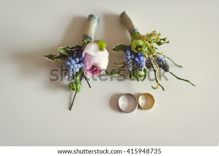 purple and pink flowers boutonniere with wedding rings on a white background  - stock photo