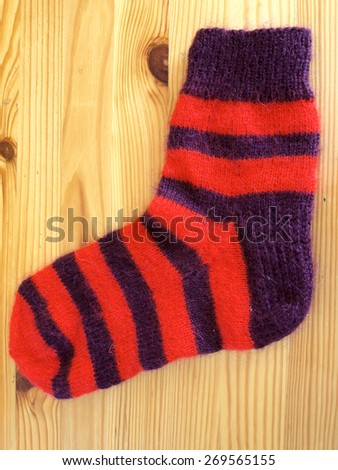 Purple and red color striped woolen sock on wooden surface vertical - stock photo