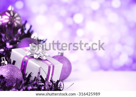 Purple and silver Christmas baubles and a gift in front of defocused purple and white lights. - stock photo