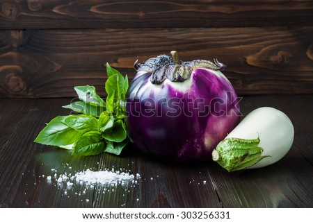 Purple and white eggplant (aubergine) with basil on dark wooden table. Fresh raw farm vegetables - harvest from the garden in rustic kitchen. Rural still life - stock photo