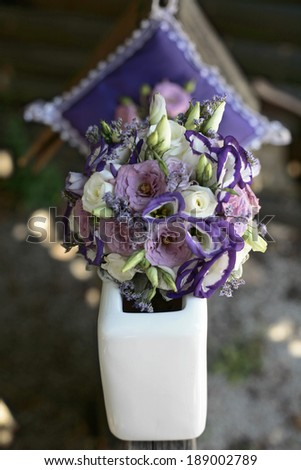 Purple and white wedding bouquet in a vase on a wooden base along with a decorative pillow - stock photo