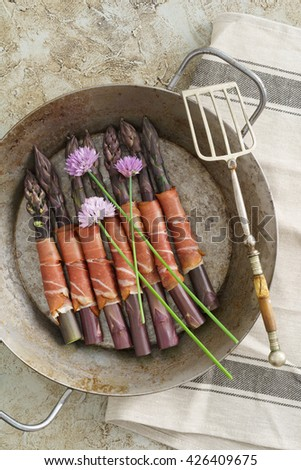 Purple asparagus wrapped with gammon in a skillet - stock photo