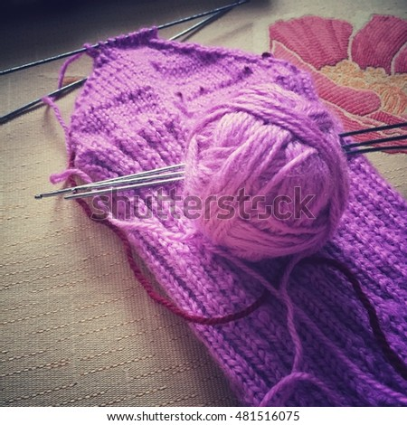 Purple ball of yarn and a crochet needles