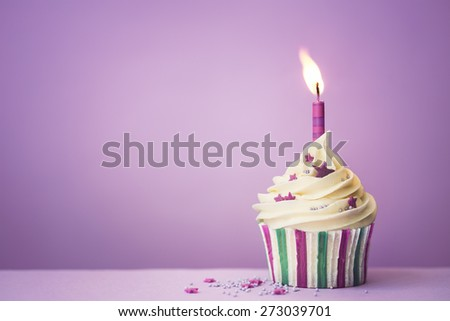 Purple birthday cupcake with copy space to side - stock photo