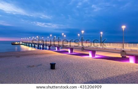Purple blue lights on the pier in the evening, Kolobrzeg, Poland - stock photo
