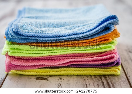 Purple, blue, pink, orange, green,yellow napkins on white wooden background - stock photo