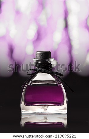 Purple bottle of perfume - stock photo