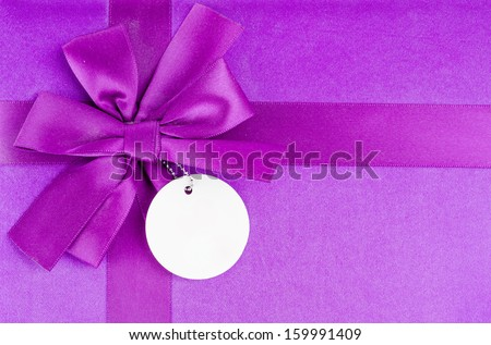 Purple bow on gift box using background - stock photo