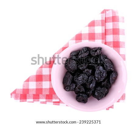 Purple bowl of prunes on checkered napkin isolated on white - stock photo