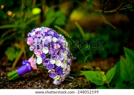 Purple bridal bouquet in the grass - stock photo