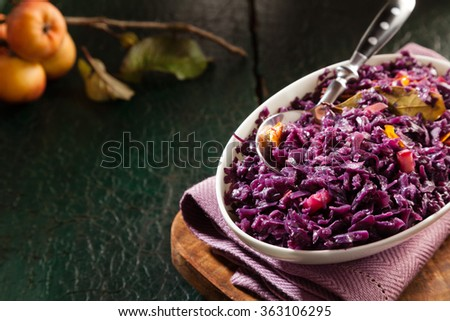 Purple cabbage in a white bowl on ancient background with copyspace. Apple flavoured delicious red cabbage on a green plate. Tasty vegan portion. - stock photo