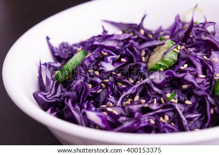Purple cabbage slaw with sesame seeds, in a white bowl dark background, close up - stock photo