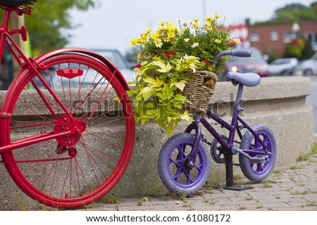 Purple child's bike behind an adult's bike as decoration - stock photo