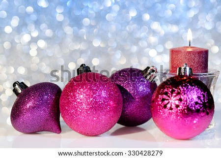 Purple Christmas balls and candle on a festive background, close up. Selective focus.