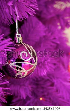 Purple Christmas bauble on purple tree - stock photo