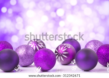 Purple Christmas baubles in front of defocused purple and white lights. - stock photo