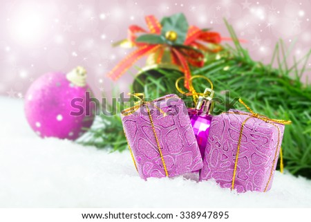 Purple Christmas gifts and ornaments against defocused lights background - stock photo