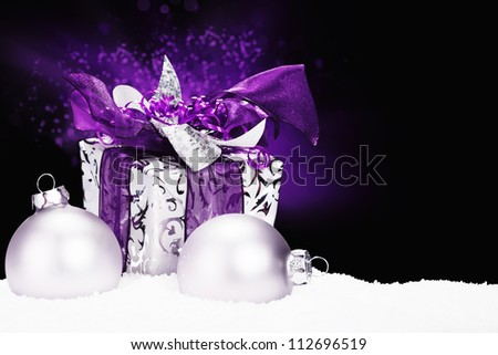 purple christmas present in snow with christmas balls and purple lightning on black background - stock photo
