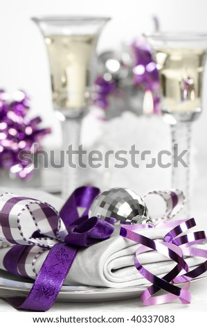 Purple Christmas table setting with napkin and glasses of white wine - stock photo