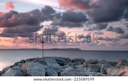 Purple cloudy sunrise at the seashore, with a sea defence groyne, silky smooth sea.Hengistbury Head, Hampshire, UK. - stock photo