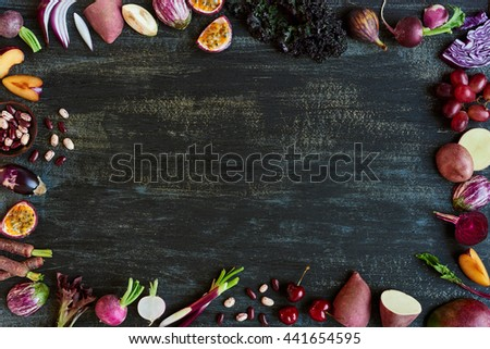 Purple coloured fruit and vegetables fresh produce on dark distressed background, plenty of copy space design element for poster, book covers, recipes, website - stock photo
