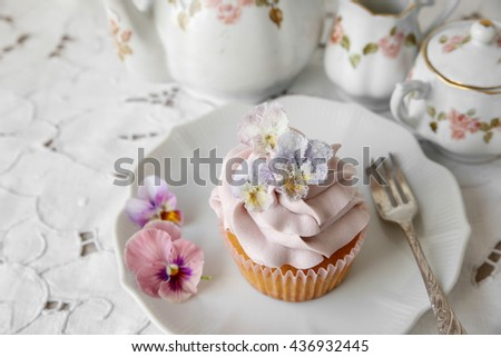 purple cupcakes with  sugared edible flowers on vintage plate