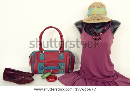 Purple dress on mannequin with matching accessories. Cute dress on tailor's dummy with purse, shoes and jewellery. - stock photo