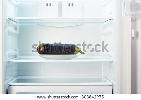 Purple eggplant on white plate in open empty refrigerator. Weight loss diet concept. - stock photo