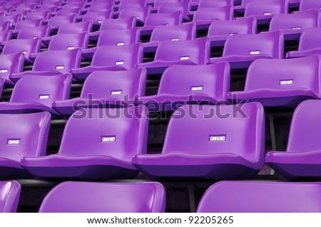 Purple Empty plastic seats at stadium open door sports arena - stock photo
