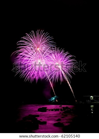 Purple fireworks launched at the shoreline of the harbor - stock photo