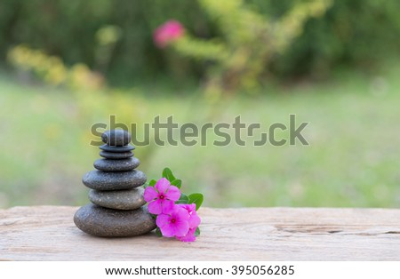 Purple flower and stone zen spa on wood with garden blurred background - stock photo