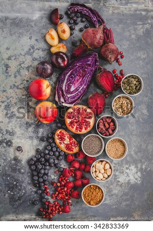 Purple fruit and veggies background with superfoods bowl. overhead on stone surface with natural light. New trend colorful rustic collage. - stock photo