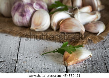 Purple garlics on a napkin on a rustic wooden table with thyme and parsley - stock photo