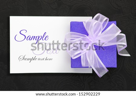 Purple gift box with ribbon on white card