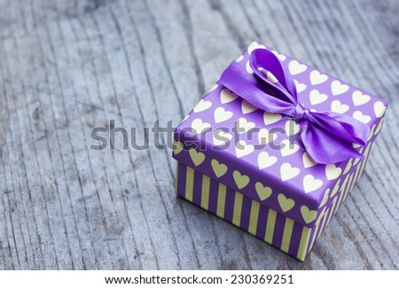 Purple gift box with yellow hearts placed  on wooden background - stock photo