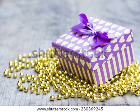 Purple gift box with yellow hearts placed upon golden pearls decoration on wooden background - stock photo