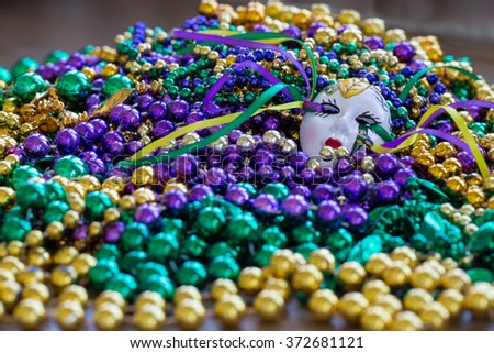 Purple, green and gold Mardi Gras beads with decorative ceramic mask (focus towards top half)