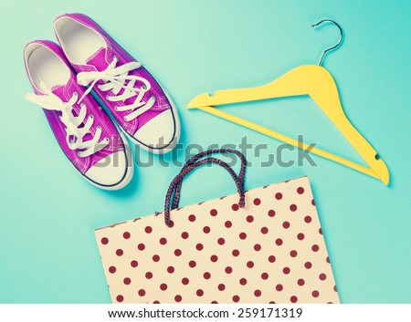 purple gumshoes with white shoelaces and hanger with shopping bag on blue background. - stock photo