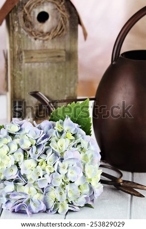 Purple Hydrangea with garden items. Extreme shallow depth of field with selective focus on flowers. - stock photo