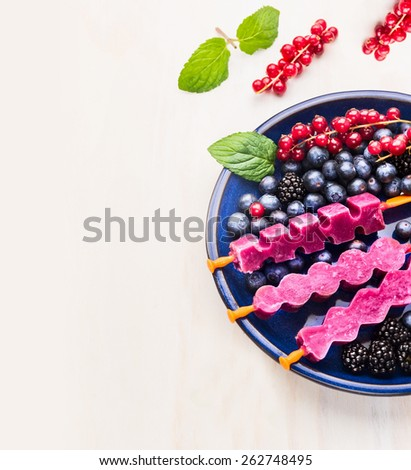 Purple  Ice cream pops  in blue plate with summer berries on white wooden background , place for text