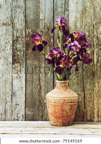 Purple iris flowers in a rustic vase on a wooden backdrop in the early morning sun with copy space. - stock photo