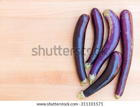 Purple japanese eggplants on wooden cutting board. - stock photo