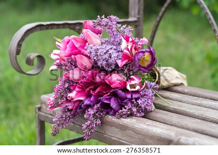 Purple lilac and tulips flower bouquet on a wooden old bench - stock photo