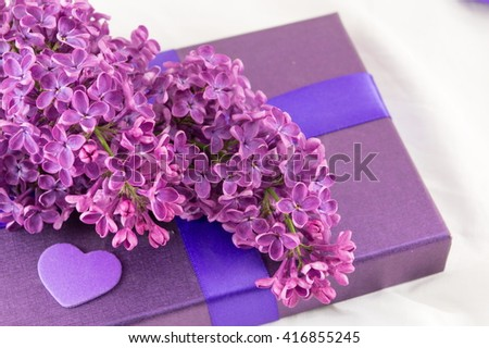Purple lilac flowers on a purple  present box - stock photo