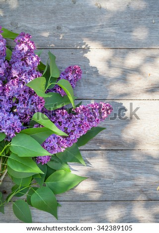 Purple lilac flowers on garden table. Top view with copy space - stock photo