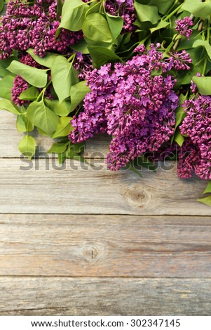 Purple lilac flowers on grey wooden background