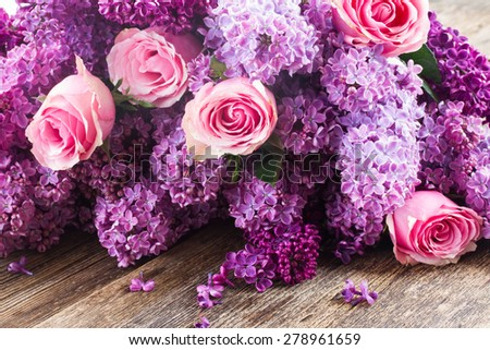 Purple Lilac flowers with pink roses on wooden table  - stock photo
