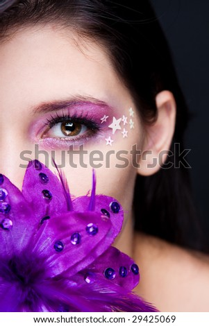 Purple make-up with stars and a purple flower - stock photo