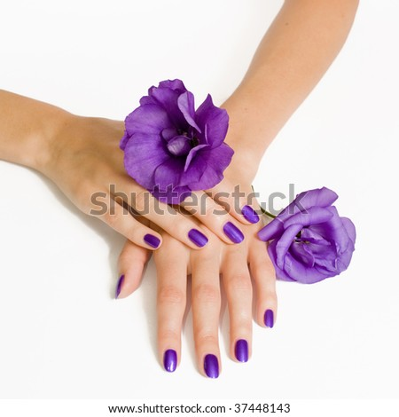 Purple manicure and violet flowers - stock photo