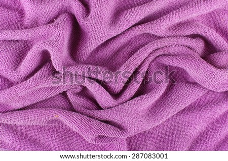 Purple microfiber cleaning cloth wrinkles abstract surface pattern - stock photo